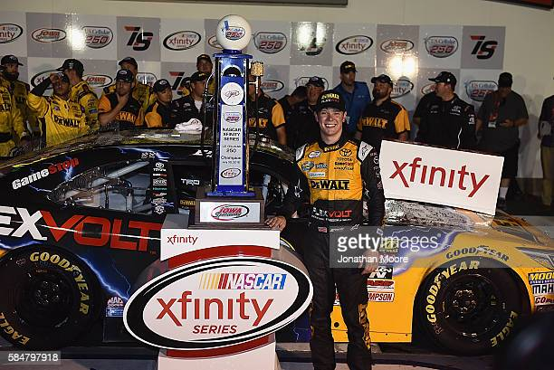 Erik Jones driver of the DeWaltToyota poses with the winner's trophy in victory lane the NASCAR XFINITY Series US Cellular 250 at Iowa Speedway on...