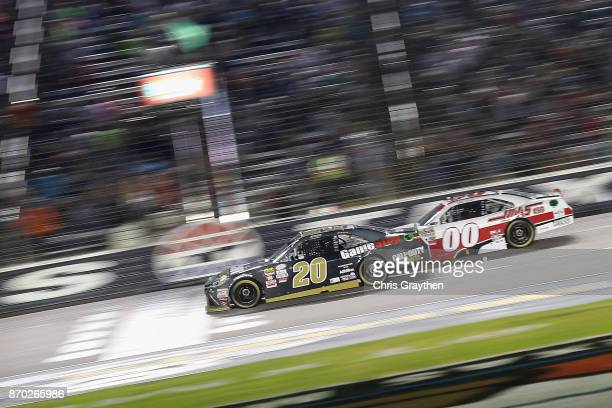 Erik Jones driver of the GameStop/Call of Duty WWII Toyota leads Cole Custer driver of the Haas Automation Ford past the green flag to start the...