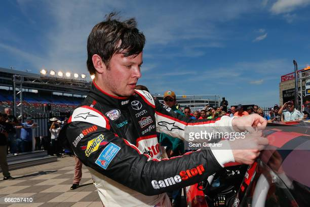 Erik Jones driver of the GameStop/GAEMS Toyota affixes the winner's decal to his car in Victory Lane after winning the NASCAR XFINITY Series My...