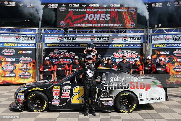 Erik Jones driver of the GameStop/Mortal Kombat X Toyota poses with the O'Reilly Auto Parts 300 Pole Award Helmet after qualifying for the pole for...