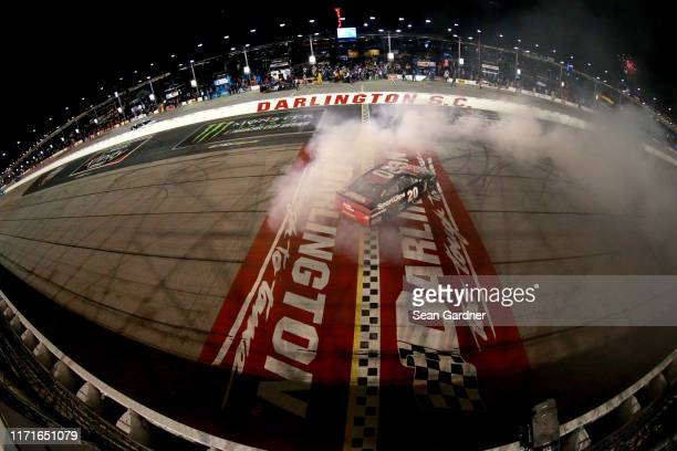 Erik Jones driver of the Sport Clips Throwback Toyota celebrates with a burnout after winning the Monster Energy NASCAR Cup Series Bojangles'...