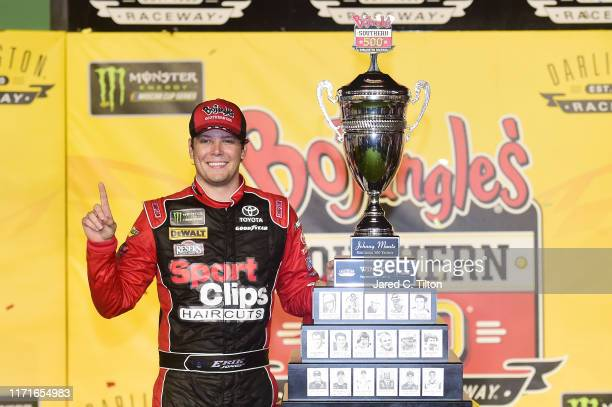Erik Jones driver of the Sport Clips Throwback Toyota poses with the trophy in Victory Lane after winning the Monster Energy NASCAR Cup Series...