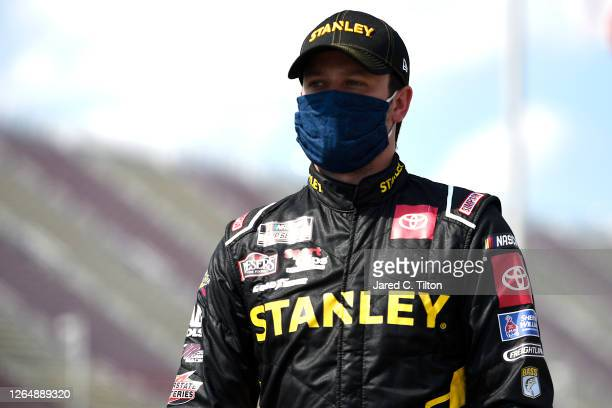 Erik Jones, driver of the STANLEY Toyota, walks the grid prior to the NASCAR Cup Series Consumers Energy 400 at Michigan International Speedway on...