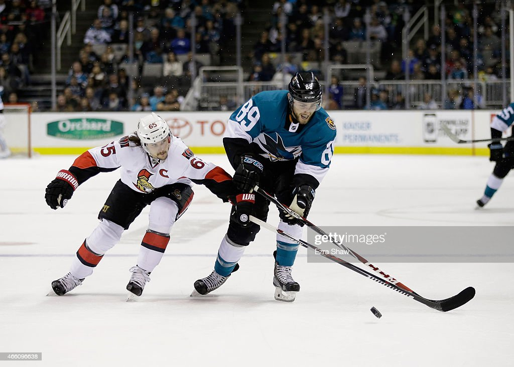 Erik Karlsson #65 of the Ottawa Senators and Barclay Goodrow #89 of the San Jose Sharks go for the puck at SAP Center on February 28, 2015 in San Jose, California.