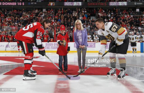Erik Karlsson of the Ottawa Senators and David Perron of the Vegas Golden Knights take a ceremonial faceoff with Nicholle Anderson and a young cancer...
