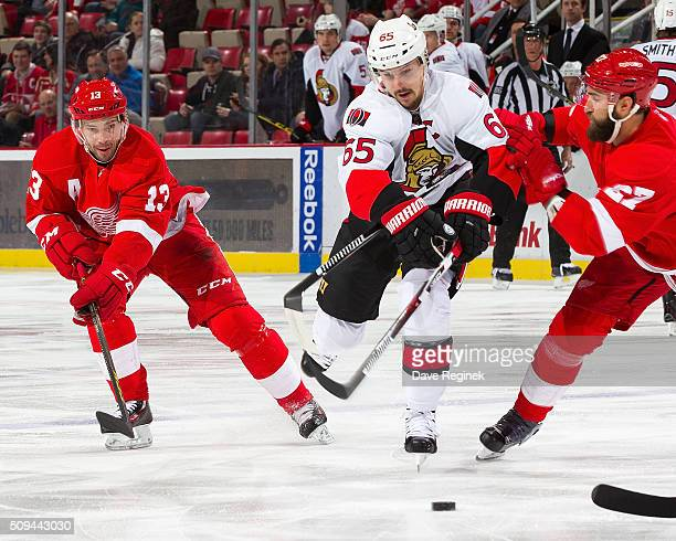 Erik Karlsson of the Ottawa Senators battles for the puck with Kyle Quincey and Pavel Datsyuk of the Detroit Red Wings during an NHL game at Joe...