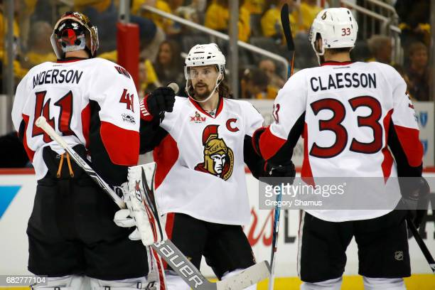 Erik Karlsson of the Ottawa Senators celebrates with Craig Anderson and Fredrik Claesson after defeating the Pittsburgh Penguins in overtime of Game...