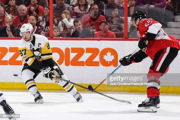 Erik Karlsson of the Ottawa Senators chips the puck past Sidney Crosby of the Pittsburgh Penguins in Game Six of the Eastern Conference Final during...