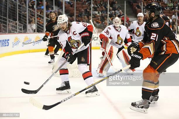 Erik Karlsson of the Ottawa Senators clears the puck past Kyle Palmieri of the Anaheim Ducks at Honda Center on February 25 2015 in Anaheim...
