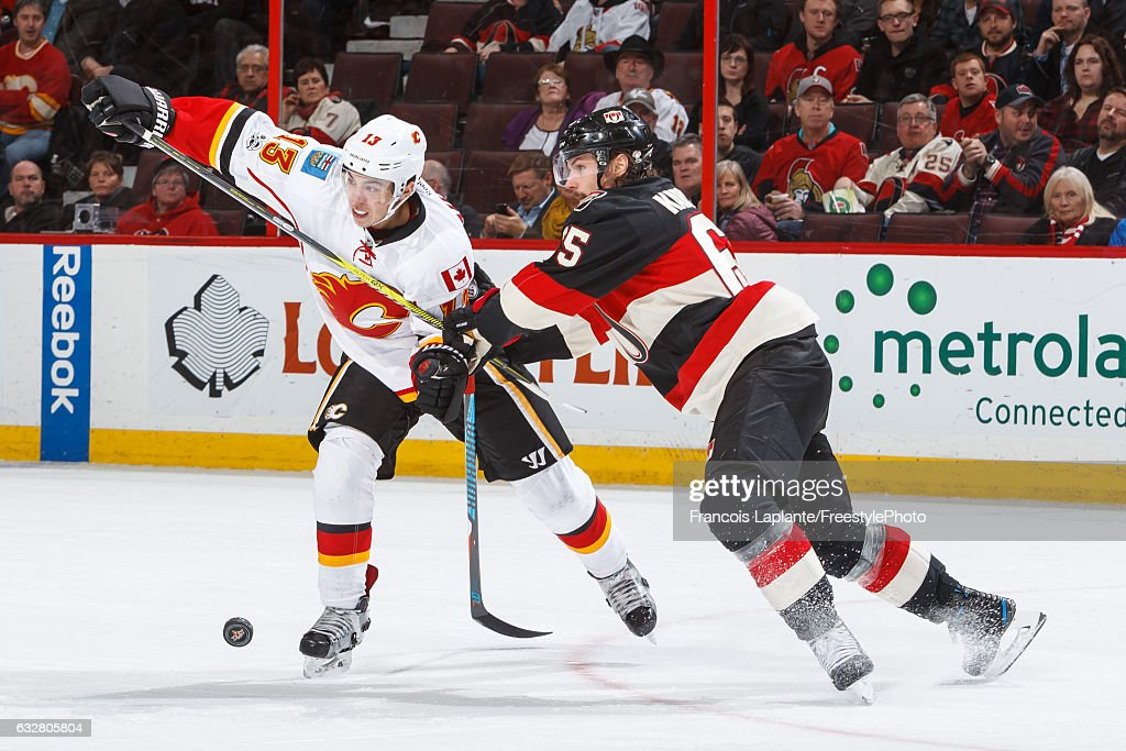 Erik Karlsson #65 of the Ottawa Senators defends against Johnny Gaudreau #13 of the Calgary Flames during an NHL game at Canadian Tire Centre on January 26, 2017 in Ottawa, Ontario, Canada.