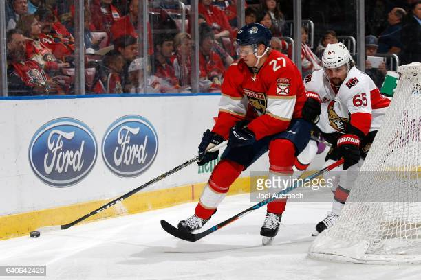 Erik Karlsson of the Ottawa Senators defends against Nick Bjugstad of the Florida Panthers as he circles the net with the puck during first period...