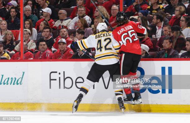Erik Karlsson of the Ottawa Senators gets checked along the boards by David Backes of the Boston Bruins in the first period in Game Five of the...
