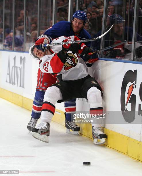 Erik Karlsson of the Ottawa Senators is checked by Brandon Prust of the New York Rangers in Game Two of the Eastern Conference Quarterfinals during...