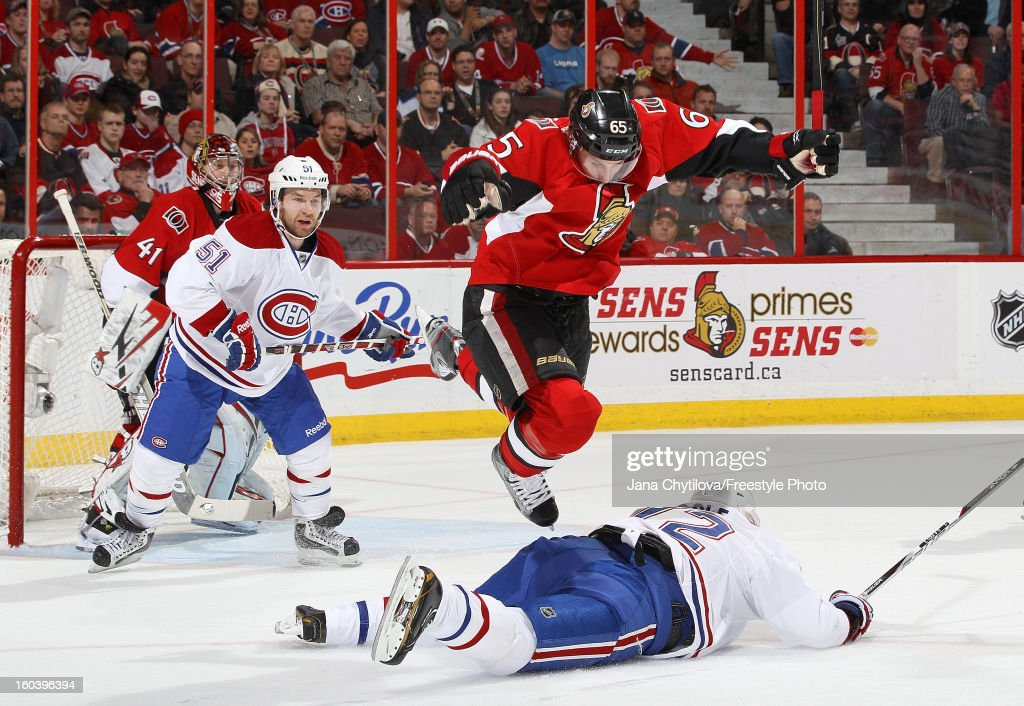 Erik Karlsson #65 of the Ottawa Senators jumps over a sprawled Erik Cole #72 of the Montreal Canadiens during an NHL game at Scotiabank Place on January 30, 2013 in Ottawa, Ontario, Canada.