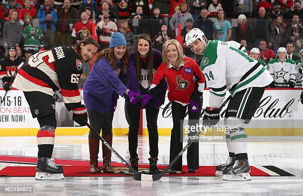 Erik Karlsson of the Ottawa Senators poses for a ceremonial faceoff with Clara Hughes Anonda Hoppner Stephanie Richardson and Jamie Benn of the...