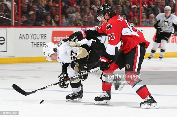 Erik Karlsson of the Ottawa Senators shoves Sidney Crosby of the Pittsburgh Penguins off the puck as they cross the blue line at Canadian Tire Centre...