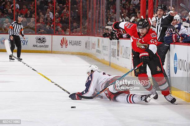 Erik Karlsson of the Ottawa Senators skates by a falling Josh Anderson of the Columbus Blue Jackets with the puck at Canadian Tire Centre on January...