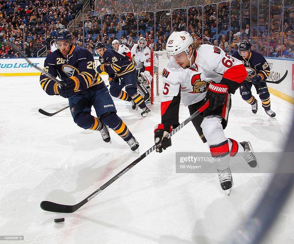 Erik Karlsson #65 of the Ottawa Senators skates with the puck against Matt Moulson #26 of the Buffalo Sabres on December 10, 2013 at the First Niagara Center in Buffalo, New York.