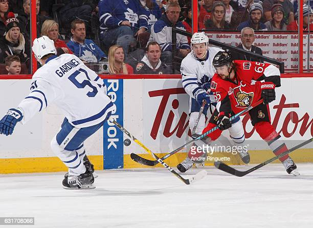 Erik Karlsson of the Ottawa Senators stickhandles the puck against Zach Hyman and Jake Gardiner of the Toronto Maple Leafs at Canadian Tire Centre on...