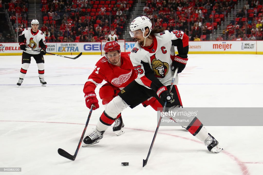 Erik Karlsson #65 of the Ottawa Senators tries to control the puck in front of Dylan Larkin #71 of the Detroit Red Wings during the third period at Little Caesars Arena on March 31, 2018 in Detroit, Michigan. Detroit won the game 2-0.