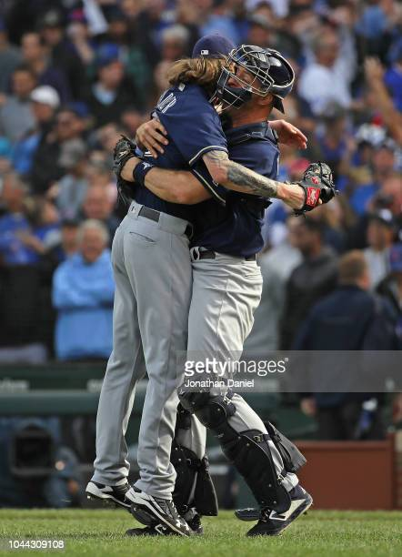 Erik Kratz of the Milwaukee Brewers hugs Josh Hader after a win over the Chicago Cubs in the National League Tiebreaker Game at Wrigley Field on...