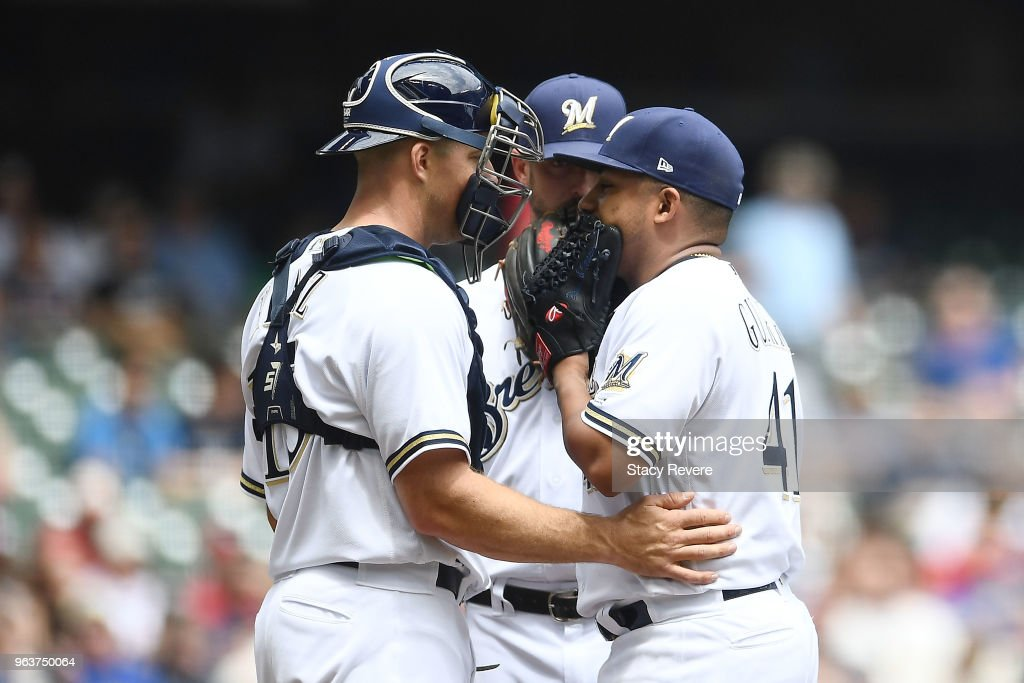 Erik Kratz #15 of the Milwaukee Brewers speaks with Junior Guerra #41 during the fifth inning of a game against the St. Louis Cardinals at Miller Park on May 30, 2018 in Milwaukee, Wisconsin.