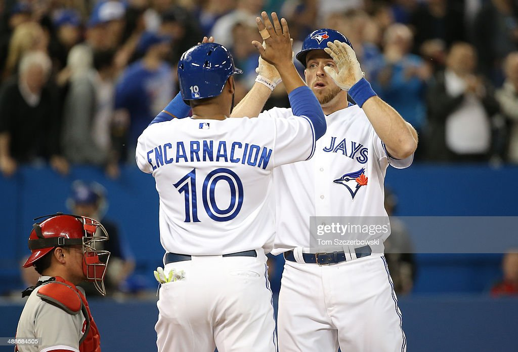 Erik Kratz #31 of the Toronto Blue Jays is congratulated by Edwin Encarnacion #10 after hitting a two-run home run in the seventh inning during MLB game action against the Philadelphia Phillies on May 7, 2014 at Rogers Centre in Toronto, Ontario, Canada.