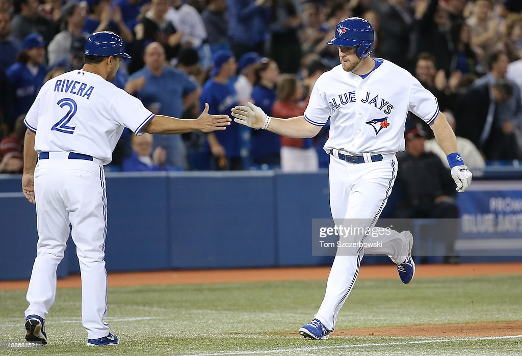 Erik Kratz #31 of the Toronto Blue Jays is congratulated by third base coach Luis Rivera #2 after hitting a two-run home run in the seventh inning during MLB game action against the Philadelphia Phillies on May 7, 2014 at Rogers Centre in Toronto, Ontario, Canada.