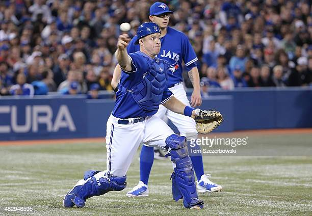Erik Kratz of the Toronto Blue Jays throws out the baserunner as Brett Cecil watches in the eighth inning during MLB game action against the New York...