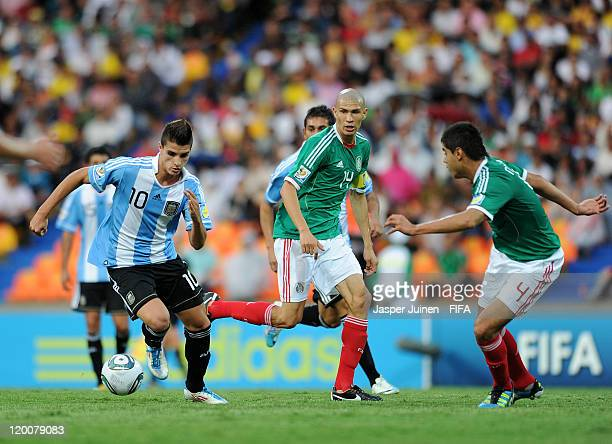 Erik Lamela of Argentina controls the ball against Jorge Enriquez and Nestor Araujo of Mexico during the FIFA U20 World Cup Colombia 2011 group F...