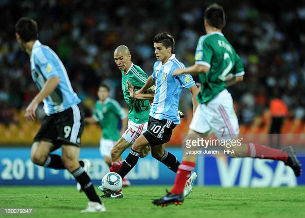 Erik Lamela of Argentina controls the ball to score the opening goal past Jorge Enriquez of Mexico during the FIFA U20 World Cup Colombia 2011 group...