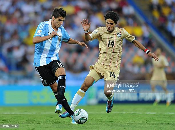 Erik Lamela of Argentina duels for the ball with Mohamed Ibrahim of Egypt during the FIFA U20 World Cup Colombia 2011 round of 16 match between...