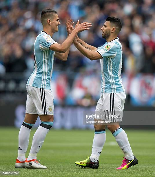 Erik Lamela of Argentina is congratulated by Sergio Aguero after scoring the first goal of his team during a group D match between Argentina and...