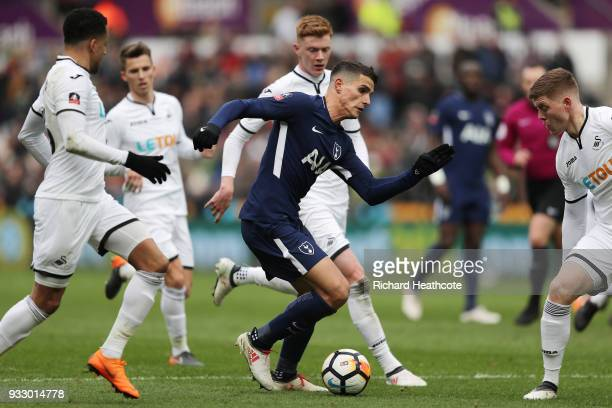 Erik Lamela of Tottenham Hotspur and Martin Olsson of Swansea City battle for the ball during The Emirates FA Cup Quarter Final match between Swansea...