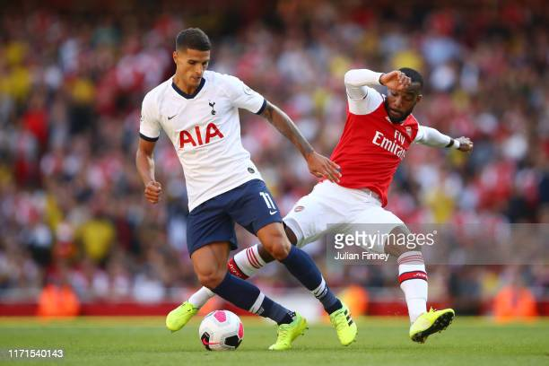 Erik Lamela of Tottenham Hotspur battles for possession with Alexandre Lacazette of Arsenal during the Premier League match between Arsenal FC and...