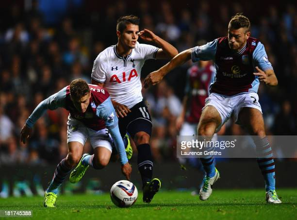 Erik Lamela of Tottenham Hotspur battles with Joe Bennett and Nathan Baker of Aston Villa during the Capital One Cup third round match between Aston...