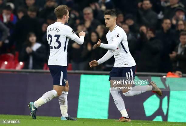 Erik Lamela of Tottenham Hotspur greets Christian Eriksen of Tottenham Hotspur as he is substituted off during the Premier League match between...