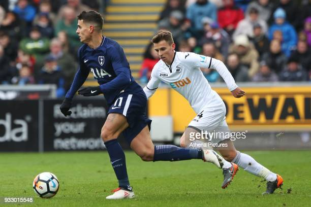Erik Lamela of Tottenham Hotspur is marked by Tom Carroll of Swansea during the Fly Emirates FA Cup Quarter Final match between Swansea City and...