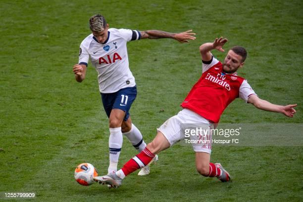 Erik Lamela of Tottenham Hotspur is tackled by Shkodran Mustafi of Arsenal during the Premier League match between Tottenham Hotspur and Arsenal FC...