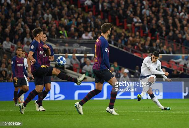 Erik Lamela of Tottenham Hotspur shoots past Gerard Pique and Clement Lenglet of Barcelona to score during the Group B match of the UEFA Champions...