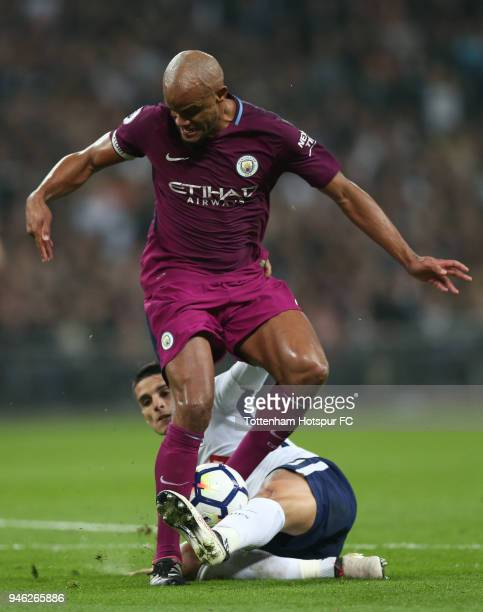 Erik Lamela of Tottenham Hotsur tackles Vincent Kompany of Manchester City during the Premier League match between Tottenham Hotspur and Manchester...