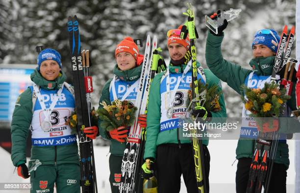 Erik Lesser of Germany, Benedikt Doll of Germany, Arnd Peiffer of Germany and Simon Schempp of Germany celebrate on the podium after the Men's...