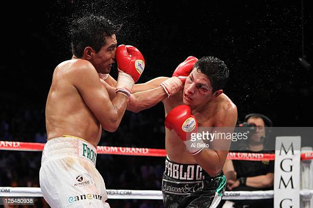 Erik Morales of Mexico and Pablo Cesar Cano of Mexico exchange blows during their WBC super lightweight title fight at the MGM Grand Garden Arena on...