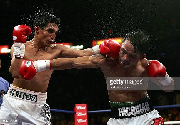 Erik Morales of Mexico throws a left at Manny Pacquiao of the Phillippines during their Super Featherweight Championship fight at Thomas Mack Arena...