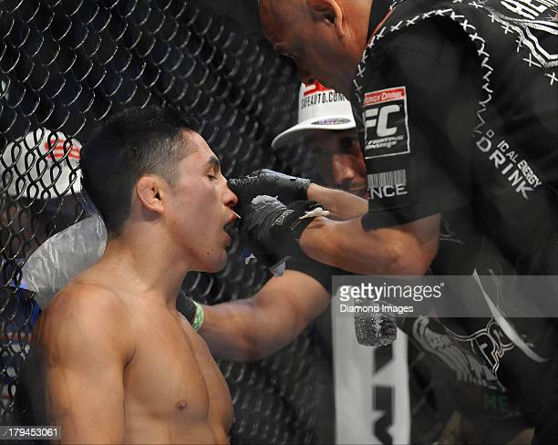 Erik Perez is checked out by the cut man in-between rounds during a bantamweight bout during UFC Fight Night 27 Condit v Kampmann 2 at Bankers Life...