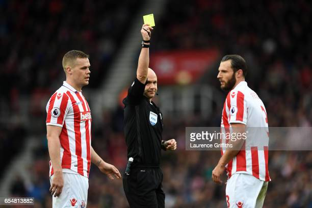 Erik Pieters of Stoke City is shown a yellow card by referee Anthony Taylor during the Premier League match between Stoke City and Chelsea at Bet365...
