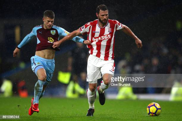 Erik Pieters of Stoke City runs with the ball under pressure from Johann Gudmundsson of Burnley during the Premier League match between Burnley and...