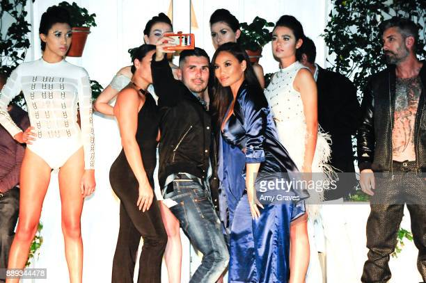 Erik Rosete poses for a photo with Models wearing the Mister Triple X Collection at the Art Hearts Fashion Holiday Couture du Couture Charity Event...