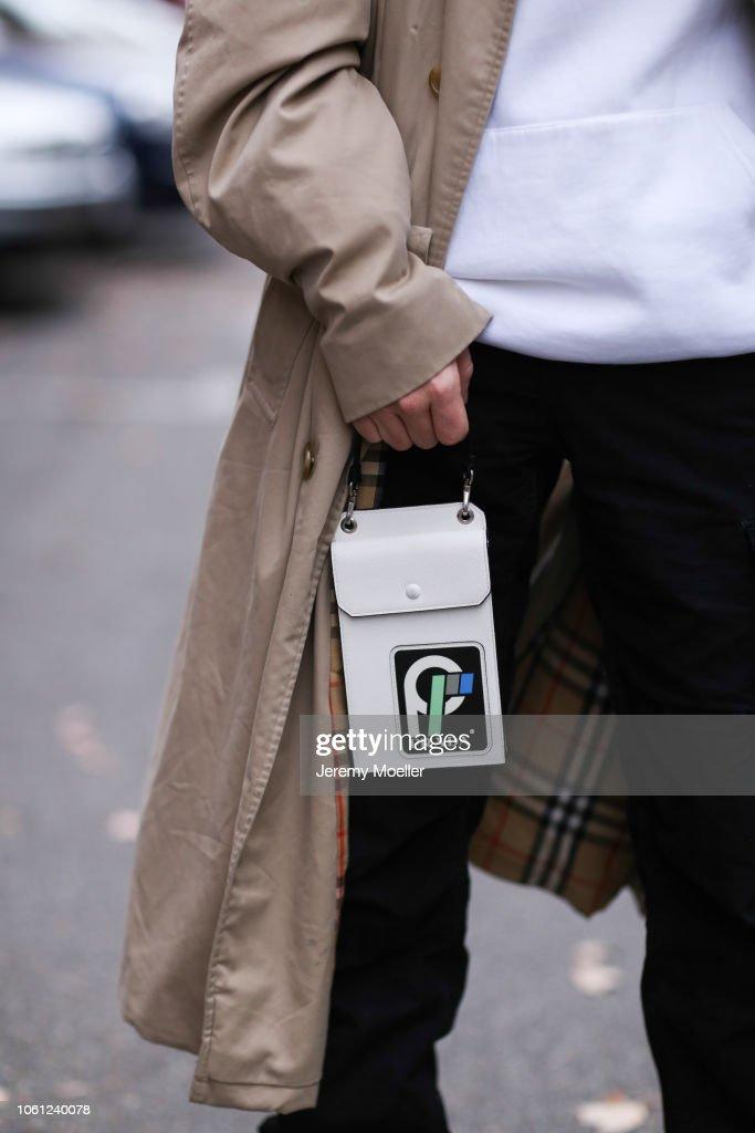 e5f71db5ef0c Erik Scholz wearing a Burberry coat and a Prada mini bag on October ...