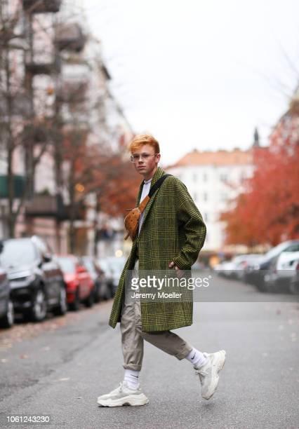 Erik Scholz wearing a MCM bag 032c belt Acne Studios shirt Balenciaga triple S and an Asos coat on October 28 2018 in Berlin Germany